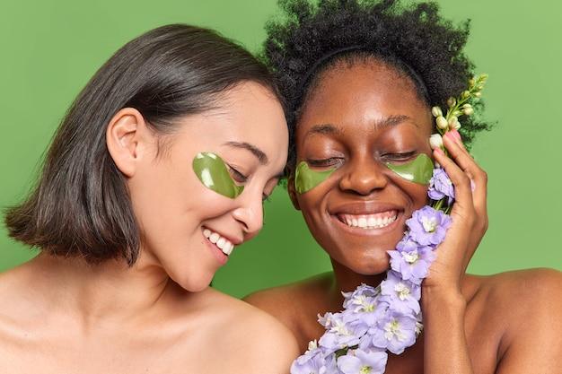 Женщины смешанной расы широко улыбаются, наносят гидрогелевые патчи под глаза, ухаживают за внешностью, держат цветок.