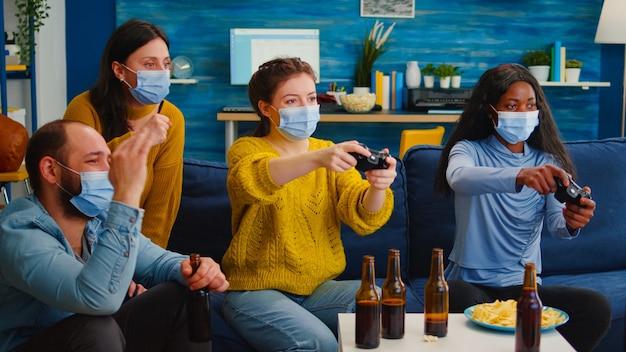 友人とリラックスした新しい通常のパーティーを楽しんでいるワイヤレスコントローラーを保持しているビデオゲームをプレイする保護マスクを持つ混血の女性。世界的大流行に対して社会的距離を保ち続ける多様な人々