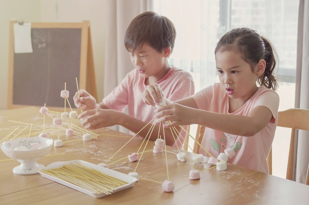 Mixed race young asian children building tower with spaghetti and marshmallow learning remotely at home, stem science, homeschooling education, social distancing, isolation concept
