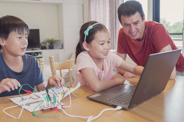 Mixed race young asian children learning coding with father, learning remotely at home, stem science, homeschooling education, social distancing, isolation concept