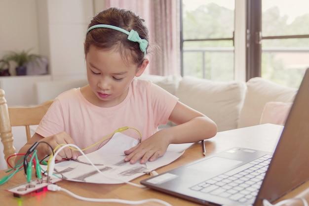 混合レースの若いアジアの女の子が一緒にコーディングを学び、子供の自宅で遠隔学習、stem科学、ホームスクーリング教育、社会的距離、分離の概念