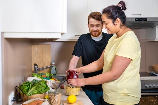 ビーガンフムスを準備している混血の若いカップル。ビーガンひよこ豆ペーストフムスを準備する魅力的な白人男性と混血の女性。ビーガン料理。快適な家庭料理。実生活の概念
