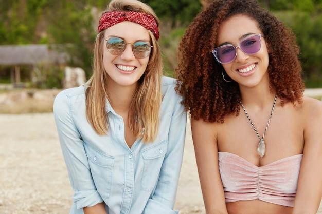 Молодые девушки-модели смешанной расы со счастливым выражением лица сидят вместе на тропическом пляже, носят солнцезащитные очки, рады встрече, демонстрируют настоящую дружбу или гомосексуальные отношения.