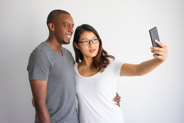 Mixed raced couple of students taking common selfie with phone.