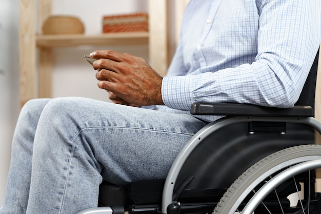 Mixed raced disabled man sitting in a wheelchair and using smartphone