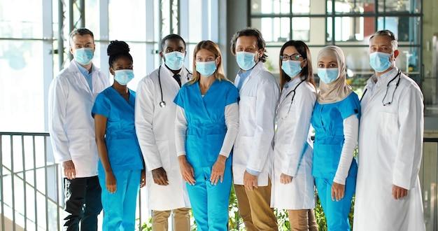 病院の専門家、男性と女性の医師の混血チーム。医療用マスクの国際的な衛生兵グループ。保護された労働者。クリニックで制服を着た多民族の医師と看護師。