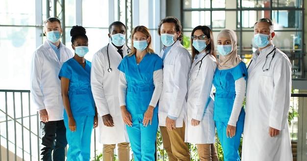 Смешанная бригада специалистов, мужчин и женщин-врачей в больнице. международная группа медиков в медицинских масках. защищенные рабочие. многонациональные врачи и медсестры в униформе в клинике.