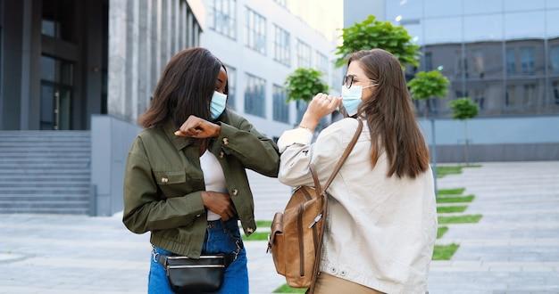 通りで会い、肘で挨拶する医療用マスクの混血の若い楽しい女性の友人。アフリカ系アメリカ人と白人の学生を元気に話したりチャットしたりする多民族の幸せな女の子。