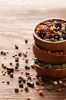 Mixed raw dried indian legumes in wooden bowls on rustic background