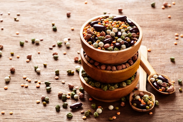 Mixed raw dried indian legumes in wooden bowls on rustic background.
