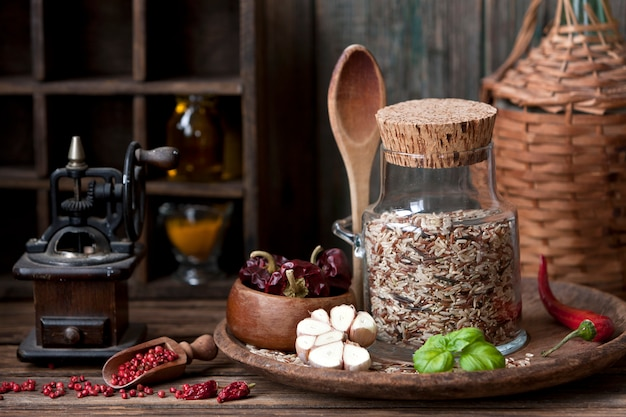 Mixed rice in glass bottle with garlic and red hot chili pepper on wooden background