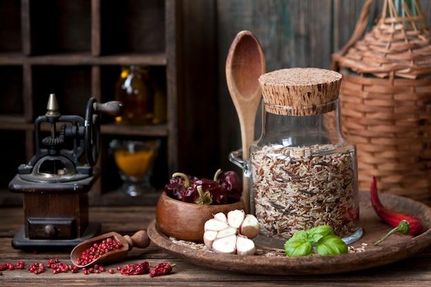 木製の背景にニンニクと赤唐辛子のガラス瓶の中の米の混合
