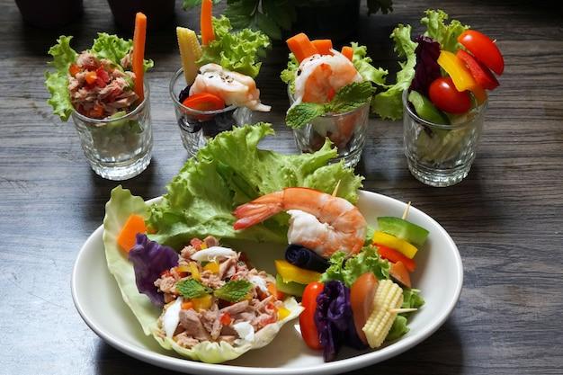 Смешанные канапе салат с заправкой в тарелке на деревянном фоне