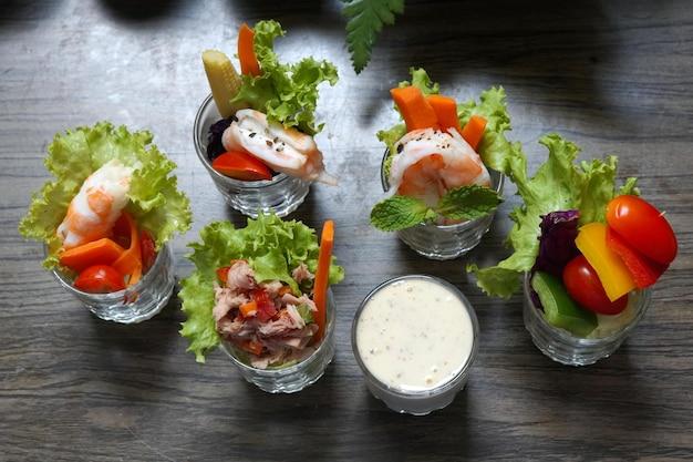 Смешанные канапы салата с заправкой в тарелке на деревянном фоне
