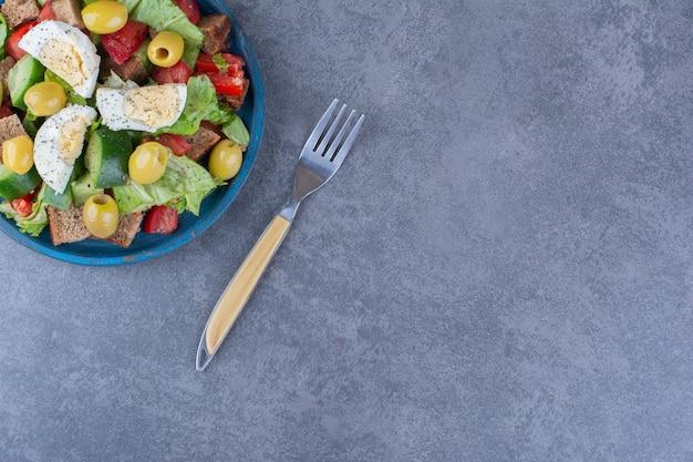 대리석 표면에 계란, 오이, 토마토, 올리브, 양상추의 혼합 샐러드