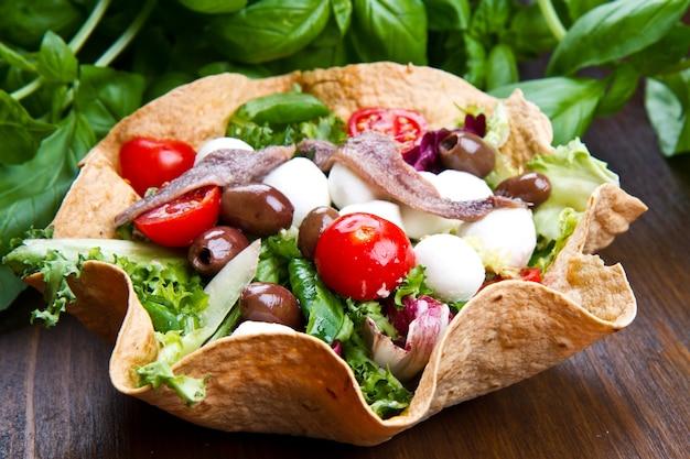 Микс салат с моцареллой и анчоусами в хлебной корзине