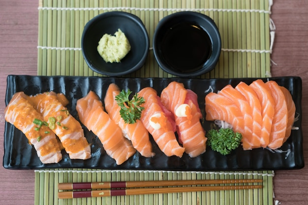 Mixed salmon sushi on black plate along with japanese sauce and green leaf decoration,