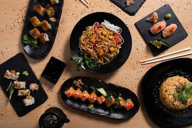 木製の背景にさまざまな日本食の混合選択。レストランメニュー。