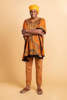 Смешанный старший индийский мужчина в желтом тюрбане и дашики