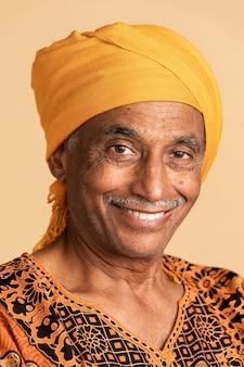 Смешанный старший индийский мужчина в желтом тюрбане