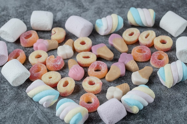 Mixed shape marshmallows and jellybeans on marble.