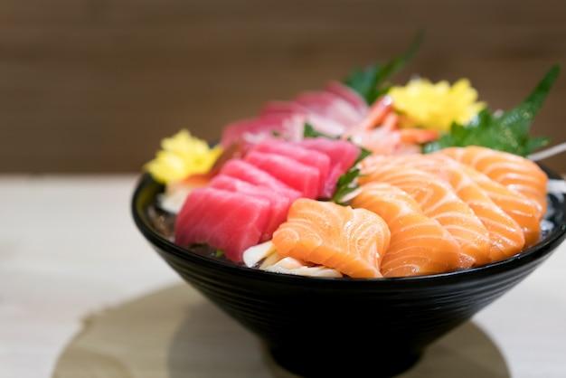 Mixed sliced fish sashimi on ice in black bowl. sashimi salmon tuna hamachi prawn and surf