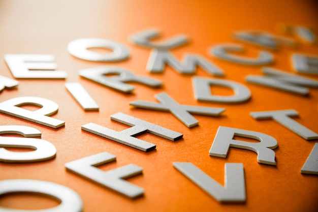 Mixed solid letters pile close up view photo. education concept on orange background.