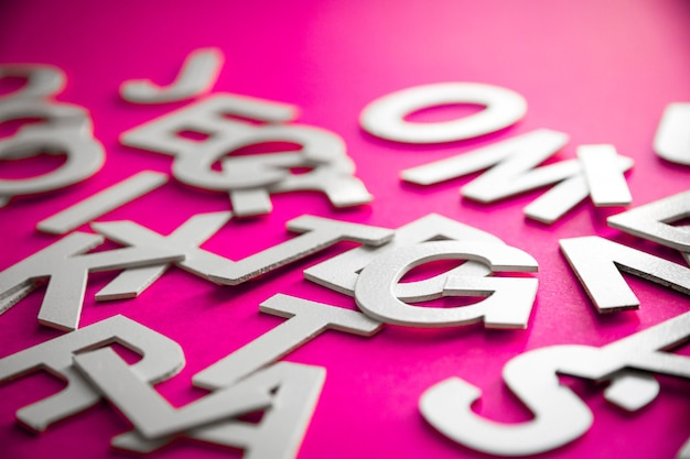 Mixed solid letters pile close up view photo. education concept on pink background.