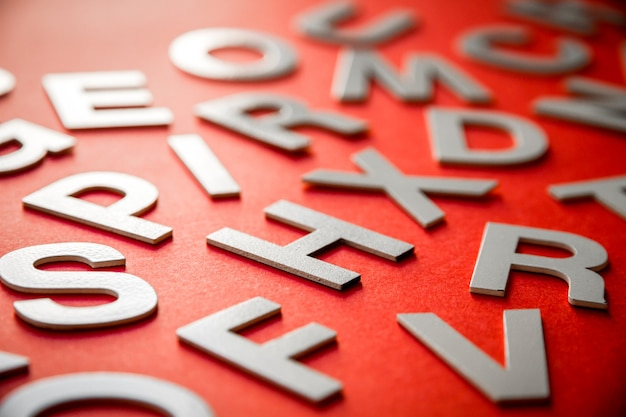 Mixed solid letters pile close up view photo. education concept on red background.