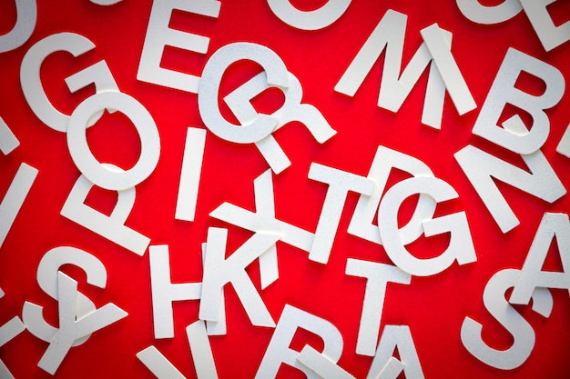 Mixed solid letters pile top view photo. education concept on red background.