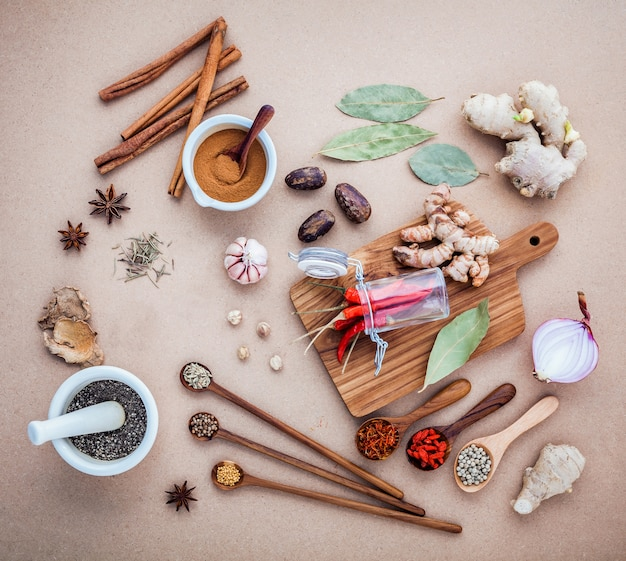 Mixed spices and herbs on brown background .