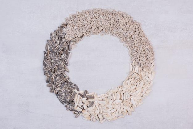 Semi di girasole misti sulla superficie bianca. Foto Gratuite