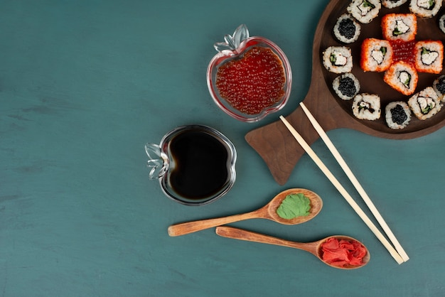 Mixed sushi plate, soy sauce and red caviar on blue surface