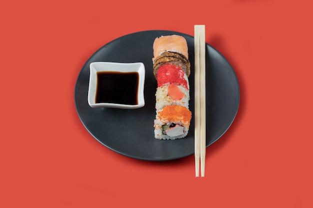 Rotoli di sushi misti in un piatto nero con salse.