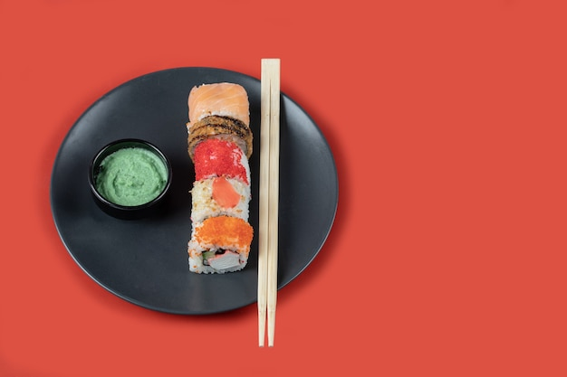 Mixed sushi rolls in a black platter with chopsticks and sauces.