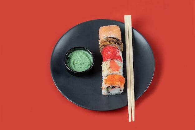 Смешанные суши-роллы в черной тарелке с соусами.