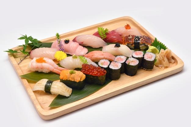 Смешанные суши в коричневый деревянный поднос на белом фоне