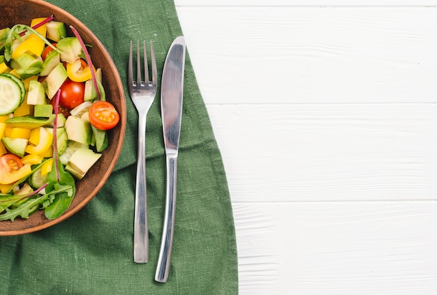 Mixed vegetable salad bowl with fork and butterknife on green tablecloth over white desk