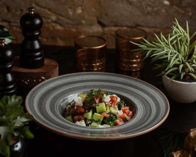 Салат из смешанных овощей, нарезанный в квадратной форме внутри серой тарелки