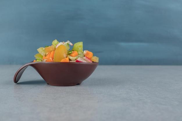 コンクリートのテーブルの上の木製のカップの混合野菜サラダ。