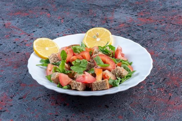 레몬 장식과 블랙 테이블에 말린 빵 껍질과 혼합 된 야채 샐러드.
