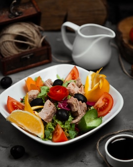 Mixed vegetable salat with boiled meat in the plate