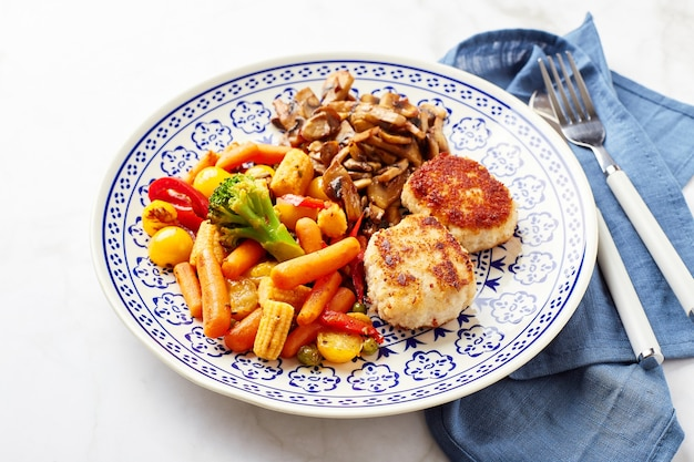 Mixed vegetables of carrots, broccoli, baby corn, bell peppers, roasted champignons and two chicken patties in breadcrumbs