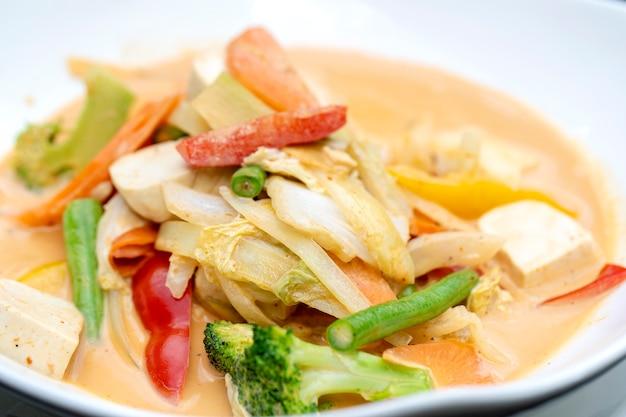 木製のテーブルの上の白いプレートに豆腐とクリーミーなレッドカレーココナッツソースの混合野菜。タイ料理、伝統的なタイ料理。