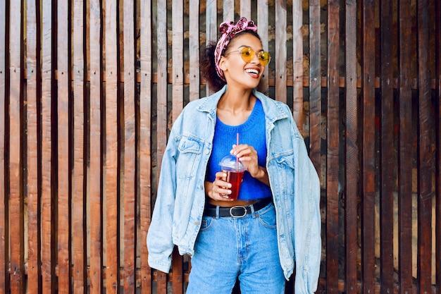 Donna mista con i capelli divertendosi, sorridendo, posando all'aperto sulla parete urbana di legno.