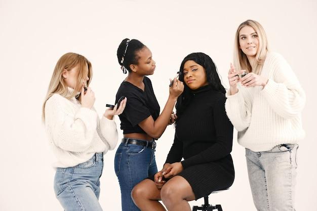 Donne miste che fanno trucco alla sua ragazza. amici multirazziali in posa isolato su sfondo bianco muro.