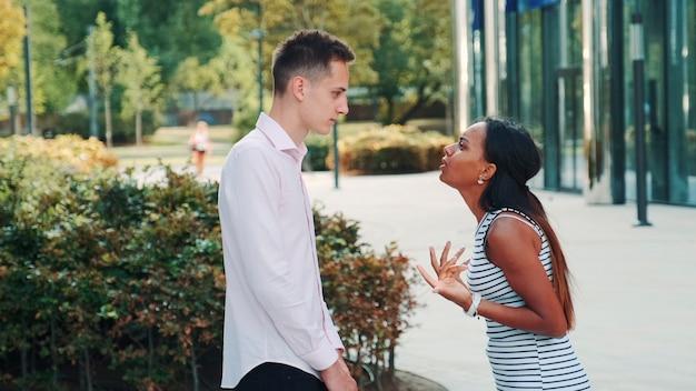 Женщина из смешанных гонок начинает плакать во время ссоры со своим парнем на улице
