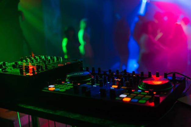 色付きライトの下でのプロフェッショナルdjディスク用のミキサーボード