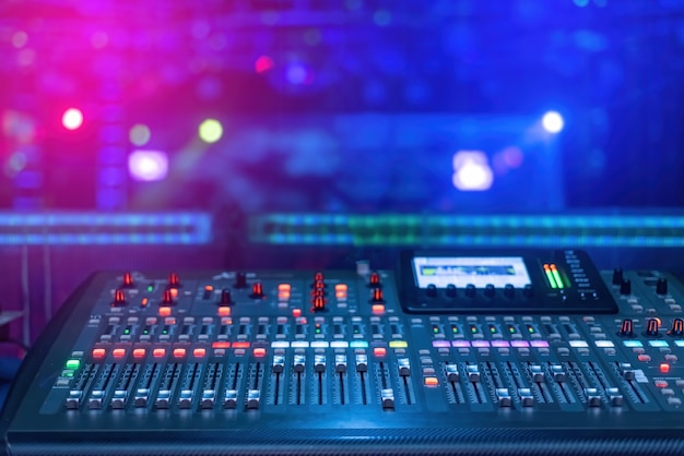 A mixer for mixing music with buttons and screen with blue and pink lights under low light conditions.