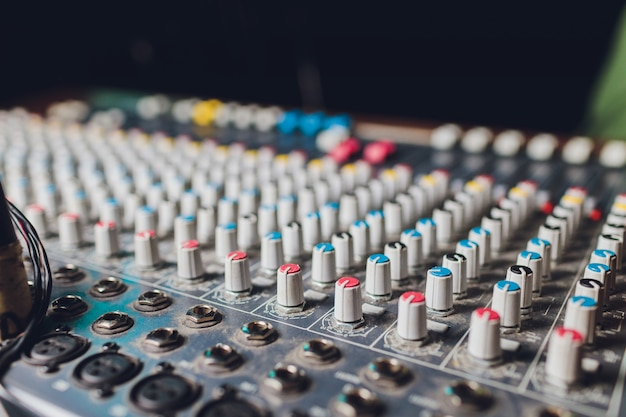 The mixer. remote for sound recording. sound engineer at work in the studio. sound amplifier mixing console equalizer. record songs and vocals. mixing tracks. audio equipment. work with musicians. dj.